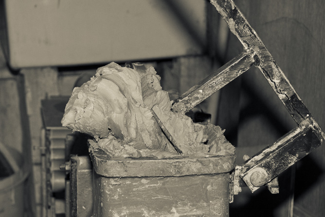Clay fed into hopper of pugmill
