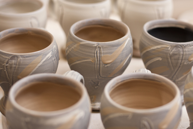 Mugs slip-decorated await salt-firing