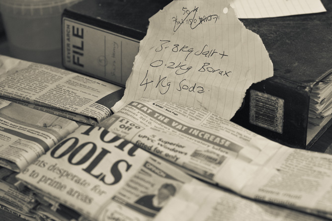 Salt packets wrapped in newspaper ready for firing